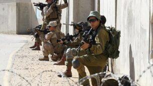 جنود مظليون إسرائيليون وأمريكيون من الكتيبة الثانية والفوج السادس من مشاة البحرية يشاركون في تدريبات خلال مناورة 'جونيبر كوبرا' العسكرية الأمريكية-الإسرائيلية المشتركة في مركز تدريب حرب المدن في 'تسياليم'، جنوب إسرائيل، 12 مارس، 2018.  (Jack Guez/AFP)