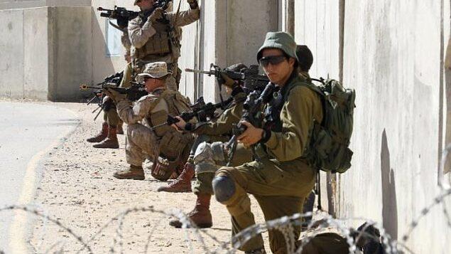 صورة توضيحية: جنود مظليون إسرائيليون وأمريكيون من الكتيبة الثانية والفوج السادس من مشاة البحرية يشاركون في تدريبات خلال مناورة 'جونيبر كوبرا' العسكرية الأمريكية-الإسرائيلية المشتركة في مركز تدريب حرب المدن في 'تسياليم'، جنوب إسرائيل، 12 مارس، 2018.  (Jack Guez/AFP)
