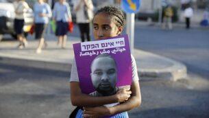 امرأة إثيوبية تحمل صورة لسولومون تيكاه، شاب من أصول إثيوبية قُتل برصاص شرطي خارج الخدمة، خلال تظاهرات أغلق فيها أبناء المجتمع الإثيوبي المدخل الرئيسي للقدس، 2 يوليو، 2019 احتجاجا على قتله. (MENAHEM KAHANA / AFP)