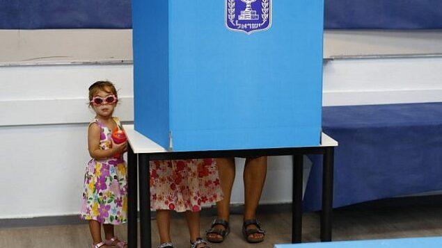طفلتان إسرائيليتان ترافقان والدهما وراء كشك اقتراع خلال الانتخابات للكنيست في مركز اقتراع في مدينة روش هعاين، 17 سبتمبر، 2019. (Jack Guez/AFP)