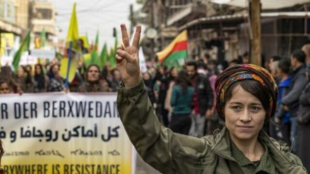 عنصر في قوات الأمن الداخلي الكردية (الأسايش) ترفع علامة النصر خلال تظاهرة ضد التهديدات التركية في مدية قامشلي بشمال شرق سوريا، العاصمة الفعلية للأقلية الكردية في سوريا، 2 نوفمبر، 2019. ( Delil SOULEIMAN / AFP)