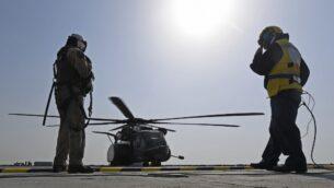 طيار أمريكي على متن سفينة 'كارديغان باي' المساعدة التابعة للأسطول البريطاني يستعد لصعود طائرة مروحية من طراز 'بلاك هوك' في رحلة استطلاعية في مياه الخليج قبالة سواحل البحرين خلال تمرين عسكري مشترك تشارك فيه أكثر من 50 دولة وسبع منظمات دولية. (KARIM SAHIB / AFP)
