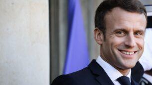الرئيس الفرنسي إيمانويل ماكرون يبتسم وهو ينتظر الضيوف في قصر الإليزيه الرئاسي قبل غداء عمل كجزء من منتدى باريس للسلام، 12 نوفمبر 2019 (LUDOVIC MARIN / AFP)