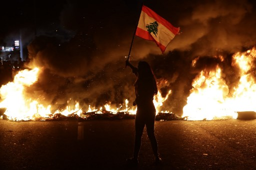 متظاهرة لبنانية مناهضة للحكومة تلوح بعلم لبناني أمام إطارات محترقة تسد الطريق الرئيسي الذي يربط مدينة طرابلس ببيروت في مدينة بيبلوس الساحلية، شمال العاصمة، 13 نوفمبر 2019. (Joseph EID / AFP)