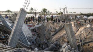 فلسطينيون يحتشدون حول أنقاض منزل يقول الجيش الإسرائيلي إنه استُخدم كمخبأ للأسلحة لحركة 'الجهاد الإسلامي'، والذي دُمر في غارة جوية إسرائيلية في خان يونس بجنوب قطاع غزة، 13 نوفمبر، 2019. (SAID KHATIB / AFP)