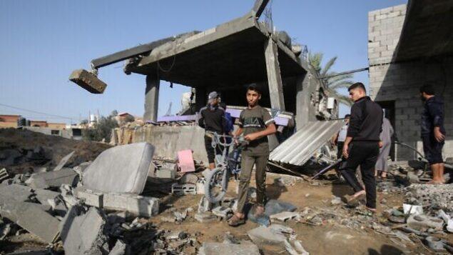 شبان فلسطينيون يبحثون عن أشياء قابلة للإصلاح وسط أنقاض منزل دُمر في غارة جوية إسرائيلية، في خان يونس بجنوب قطاع غزة، 13 نوفمبر، 2019.  (SAID KHATIB / AFP)