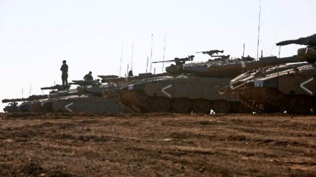 جندي إسرائيلي يقف على دبابة من طراز 'مركافا' متمركزة في هضبة الجولان، 20 نوفمبر، 2019. (JALAA MAREY / AFP)