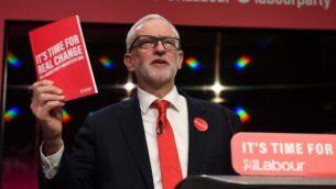 زعيم حزب 'العمال' البريطاني المعارض، جيريمي كوربين، يحمل نسخه من البرنامج الإنتخابي للحزب، خلال كلمة ألقاها في حدث أقيم لإطلاق البرنامج الإنتخابي للحزب في برمنغهام، شمال غرب انجلترا، 21 نوفمبر، 2019. (Oli Scarff/AFP)