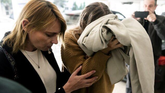 شابة بريطانية (يمين) متهمة بالادعاء كذباً بأنها تعرضت للاغتصاب على أيدي سياح إسرائيليين، تغطي وجهها وهي تصل لمحكمة فاماغوستا، في بارالمني بشرق قبرص، 28 نوفمبر 2019 (Iakovos Hatzistavrou / AFP)
