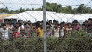 لاجئون من الروهينغيا يتجمعون بالقرب من سياج خلال جولة إعلامية نظمتها الحكومة في المنطقة بين ميانمار وبنغلاديش، بالقرب من قرية تونجبيولياتيار، مونغ داو، ولاية راخين الشمالية، ميانمار، 29 يونيو 2018. (Min Kyi Thein/AP)