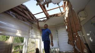 رجل يتفقد الأضرار التي لحقت بمنزل في سديروت، إسرائيل، بعد أن أصيب بصاروخ تم إطلاقه من قطاع غزة، 12 نوفمبر، 2019. (AP Photo/Tsafrir Abayov)