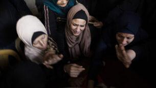 أقارب الناشط في حركة 'الجهاد الإسلامي'، عبد الله البلبيسي (26 عاما)، الذي قٌتل في غارة جوية إسرائيلية، خلال جنازته في مدينة بيت لاهيا، شمال قطاع غزة، 13 نوفمبر، 2019.  (AP Photo/Khalil Hamra)