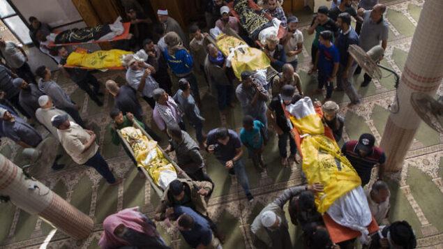 فلسطينيون يحملون جثامين رسمي أبو ملحوس وسبعة من أفراد عائلته، الذين قُتلوا في غارة جوية إسرائيلية استهدفت مزلهم، خلال جنازتهم في مسجد في بلدة دير البلح، وسط قطاع غزة، 14 نوفمبر، 2019.  (AP Photo/Khalil Hamra)