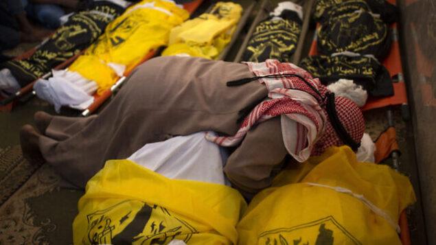 فلسطيني يودع جثامين  رسمي أبو ملحوس وسبعة من أفراد عائلته الذين قُتلوا في غارة ليلية إسرائيلية استهدفت منزلهم، في مسجد خلال مراسم جنازتهم، في دير البلح، وسط قطاع غزة، 14 نوفمبر، 2019.  (AP Photo/Khalil Hamra)