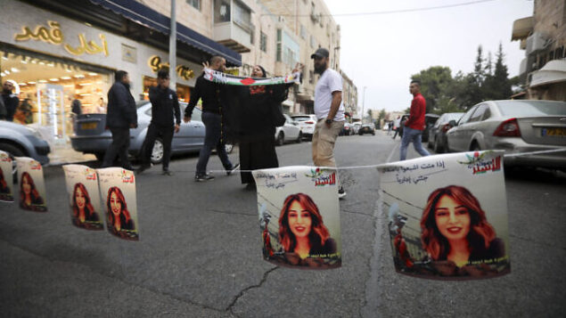 فلسطينيون يعلقون صور لهبة اللبدي، مواطنة أردنية من أصول فلسطينية، خلال تظاهرة للمطالبة بإطلاق سراحها في القدس الشرقية، 26 أكتوبر، 2019. (AP/Mahmoud Illean)