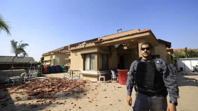 شرطي يقف أمام منزل أصيب بصاروخ أطلِق من قطاع غزة في مدينة نتيفوت، إسرائيل، 12 نوفمبر، 2019. (Tsafrir Abayov/AP)