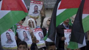 متظاهرون يحملون الأعلام الفلسطينيون ولافتات تحمل صور الأسير الفلسطيني في السجون الإسرائيلية، سامي أبو دياك، الذي توفي بعد صراع مع مرض السرطان، خلال تظاهرة في مدينة رام الله بالضفة الغربية، 26 نوفمبر، 2019.  (AP Photo/Nasser Nasser)