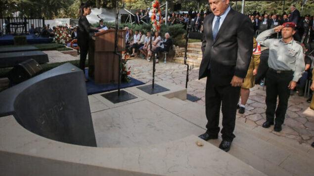 رئيس الوزراء بنيامين نتنياهو يقف أمام ضريح رئيس الوزراء الراحل يتسحاق رابين خلال مراسم لإحياء الذكرى ال23 لاغتياله في مقبرة جبل هرتسل بالقدس، 21 أكتوبر، 2018.  (Marc Israel Sellem/POOL )