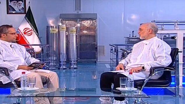 لقطة شاشة من مقطع فيديو يظهر فيه علي أكبر صالحي، رئيس منظمة الطاقة الذرية الإيرانية (يمين) وفي الخلفية ثلاثة أجهزة طرد مركزي لتخصيب اليوارنيوم إيرانية الصنع. (YouTube)