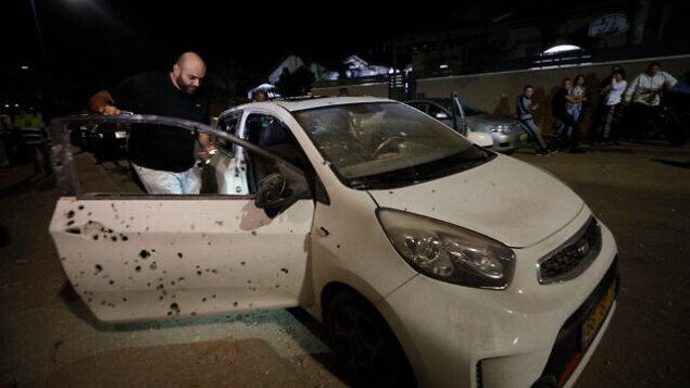 رجل يقوم بتفقد مركبة أصيبت بشظايا قذيفة صاروخية أطلقت من غزة على مدينة سديروت الإسرائيلية ، 1 نوفمبر، 2019. (AP Photo/Tsafrir Abayov)
