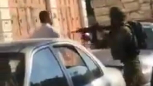 جندي إسرائيلي يوجه سلاحه تجاه رجل فلسطيني أمام طفله في الخليل، 5 نوفمبر، 2019. (Screenshot: Twitter)