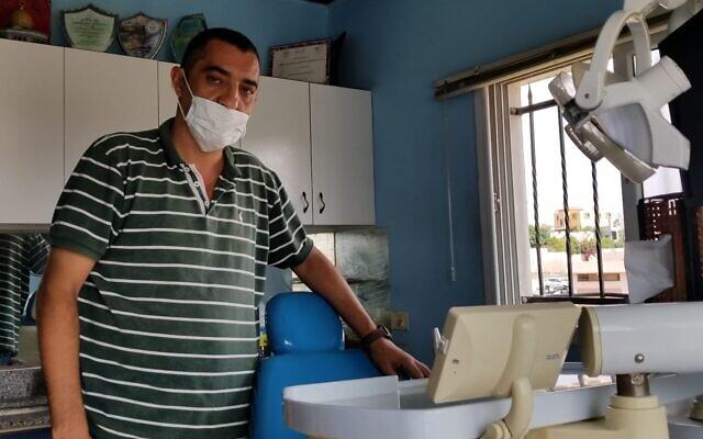 أمين منصور (47 عاما)، طبيب أسنان من قرية عزون الفلسطينية بالضفة الغربية يقف في عيادته، 20 أكتوبر، 2019. (Adam Rasgon/ Times of Israel)