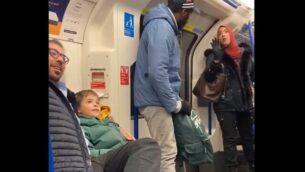 سيدة مسملة (يمين) تحاول منع رجل من توجيه إساءات معادية للسامية لعائلة يهودية مع أطفال صغار السن في مترو لندن، 22 نوفمبر، 2019.  (Screencapture/Twitter)