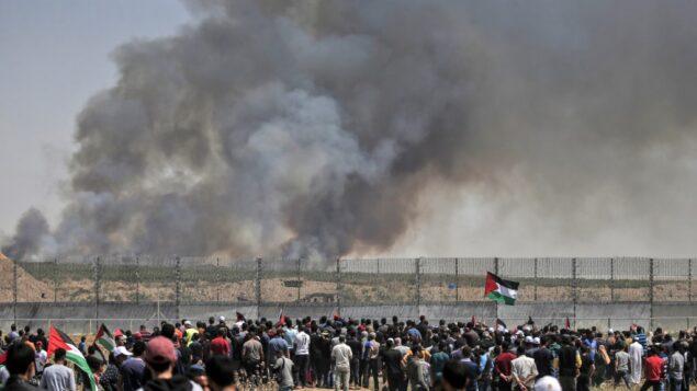 فلسطينيون يتظاهرون امام السياج الحدودي مع اسرائيل شرقي مدينة غزة، بينما يتصاعد الدخان من حرائق ناتجة عن بالونات حارقة، 15 مايو 2019 (MAHMUD HAMS / AFP)