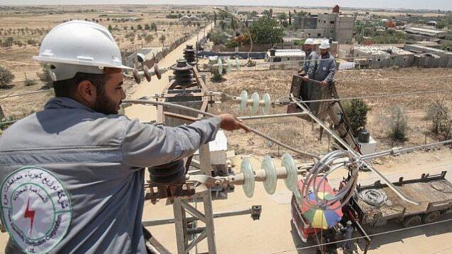 توضيحية: عمال كهرباء فلسطينيين يتفقدون منشآت كهرباء في مدينة رفج بجنوب غزة،  25 يونيو، 2019.(Said Khatib/AFP)