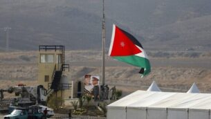 صورة تم التقاطها للجانب الإسرائيلي للحدود يظهر فيها جنود أردنيون وهم يرفعون العلم الأردني قبيل مراسم في موقع الباقورة (نهارييم)، 10 نوفمبر، 2019. (Menahem Kahana/AFP)