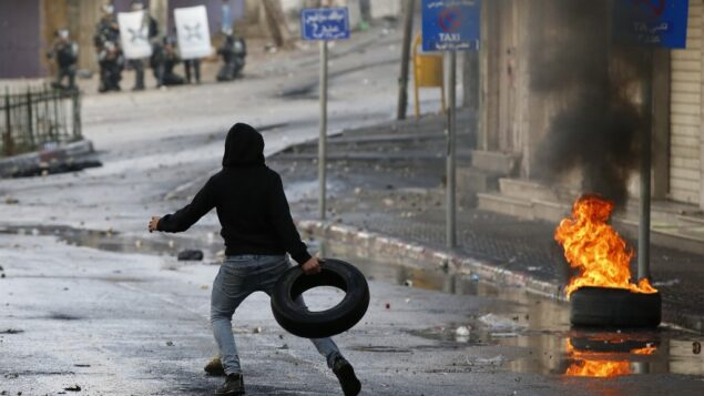 متظاهر فلسطيني يرمي إطارًا أثناء أثناء اشتباكات مع قوات الأمن الإسرائيلية في مدينة الخليل جنوب الضفة الغربية، 9 ديسمبر 2019، وسط إضراب عام احتجاجا على النشاط الاستيطاني الإسرائيلي. (HAZEM BADER / AFP)