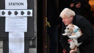 رئيس الوزراء البريطاني بوريس جونسون في صورة مع كلبه، ديلين، خلال مغادرته لمركز اقتراع بعد أن أدلى بصوته في وسط لندن، 12 ديسمبر، 2019، حيث تجري بريطانيا انتخابات عامة.  ( DANIEL LEAL-OLIVAS / AFP)