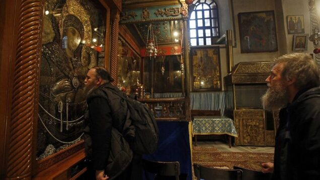 أحد الحجاج المسيحيين يقبل أيقونة السيدة العذراء في كنيسة المهد، الموقع الذي يعتقد المسيحيون أنه المسيح ولد فيه، في مدينة بيت لحم بالضفة الغربية، 18 ديسمبر 2019. (Musa Al Shaer/AFP)