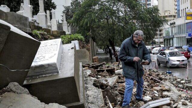 رجل يتفقد القبور التي لحقت بها أضرار أثناء عاصفة شتوية في المقبرة اليهودية في العاصمة اللبنانية بيروت. (Anwar Amro/AFP)