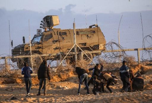 متظاهرون فلسطينيون يرشقون القوات الإسرائيلية بالحجارة على الحدود بين إسرائيل وغزة، شرق رفح في جنوب القطاع، 27 ديسمبر 2019. (SAID KHATIB / AFP)
