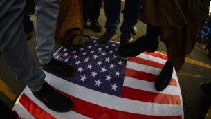 عراقيون يدوسون على العلم الأمريكي، خلال مظاهرة في مدينة النجف، للتنديد بالهجمات التي شنتها الطائرات الأمريكية في الليلة الماضية على عدة قواعد تابعة لكتائب حزب الله المدعومة من إيران، 30 ديسمبر 2019 (Haidar HAMDANI/AFP)