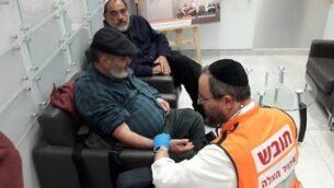 مسعف يقوم بفحص دافيد بن أفراهام (وسط) بعد إطلاقه سراحه من السجن الفلسطيني، وإلى جانبه يجلس صديقه حاييم بيريغ. (United Hatzalah)