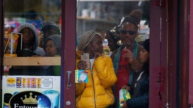 متفرجون يطلون من أحد المتاجر مع وصول قوى الأمن إلى موقع إطلاق نار، 10 ديسمبر، 2019، في مدينة جيرسي سيتي بولاية نيو جيرسي. (Photo/Eduardo Munoz Alvarez)