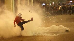 متظاهر مناهض للحكومة يركل عبوة غاز مسيل للدموع عودة الى شرطة مكافحة الشغب، أثناء مظاهرة بالقرب من ساحة البرلمان، في وسط بيروت، لبنان، 15 ديسمبر 2019. (AP Photo / Hussein Malla)