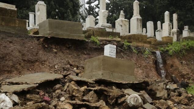 قبور مقبرة يهودية تقع على رصيف بعد أن انهارت نتيجة هطول أمطار غزيرة في منطقة السوديكو في بيروت، لبنان، 26 ديسمبر 2019. (AP Photo / Hassan Ammar)