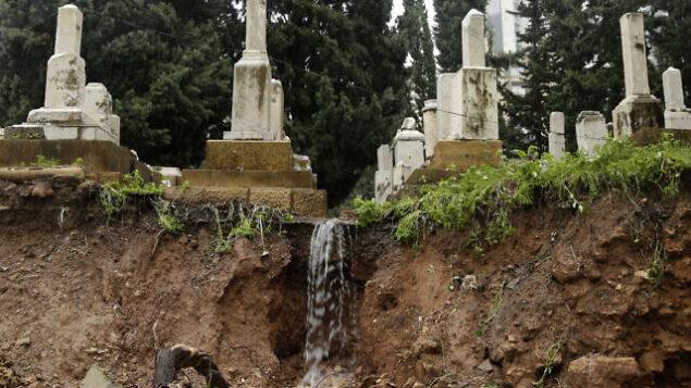 اشخاص يتفحصون القبور التي لحقت بها أضرار أثناء عاصفة شتوية في المقبرة اليهودية في العاصمة اللبنانية بيروت. (Anwar Amro/AFP)