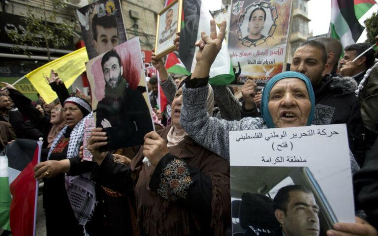 أقارب فلسطينيين محتجزين في السجون الإسرائيلية يحملون صورهم أثناء مظاهرة بمناسبة 'يوم الاسرى' في مدينة رام الله بالضفة الغربية، 7 أبريل 2019. (AP Photo/Majdi Mohammed)