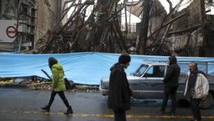 صورة توضيحية: اشخاص يسيرون امام مباني أحرقت أثناء الاحتجاجات الأخيرة، في شهريار، إيران، على بعد حوالي 40 كيلومترًا جنوب غرب العاصمة طهران، 20 نوفمبر 2019. (Vahid Salemi/AP)