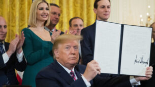 President Donald Trump shows the executive order he signed combatting anti-Semitism in the U. S. during a Hanukkah reception in the East Room of the White House Wednesday, Dec. 11, 2019, in Washington. (AP Photo/Manuel Balce Ceneta)