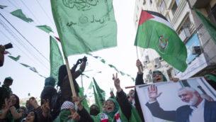نساء فلسطينيات، تحمل إحدىهن صورة لزعيم حركة حماس إسماعيل هنية، يحضرن مظاهرة حاشدة للاحتفال بالذكرى الثانية والثلاثين لتأسيس حماس، في مدينة غزة، 14 ديسمبر 2019 (AP/Khalil Hamra)