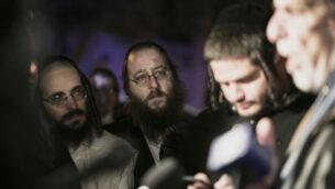 يهود متشددون يستمعون إلى عضو مجلس النواب السابق في نيويورك دوف هيكيند يتحدث في مونسي، نيويورك، 29 ديسمبر 2019، بعد هجوم طعن وقع مساء السبت خلال احتفال حانوكا. (AP/Allyse Pulliam)