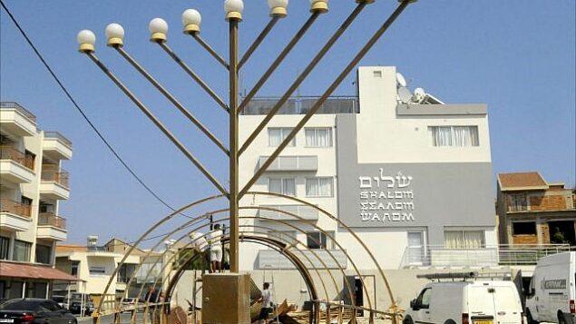 توضيحية: عمال بناء يعملون على إطار  كوخ  Qonaset من فترة الحرب العالمية الثانية أمام مركز الجالية اليهودية في لارنكا، قبرص.  (Larry Luxner/Times of Israel)