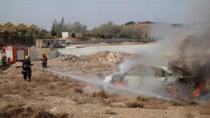 عناصر إطفاء يخمدون حريقا في مركبة خلال تمرين للجيش الإسرائيلي يحاكي هجوما صاروخيا في مستوطنة كفار أدوميم بوسط الضفة الغربية، 11 ديسمبر، 2019.  (Judah Ari Gross/The Times of Israel)