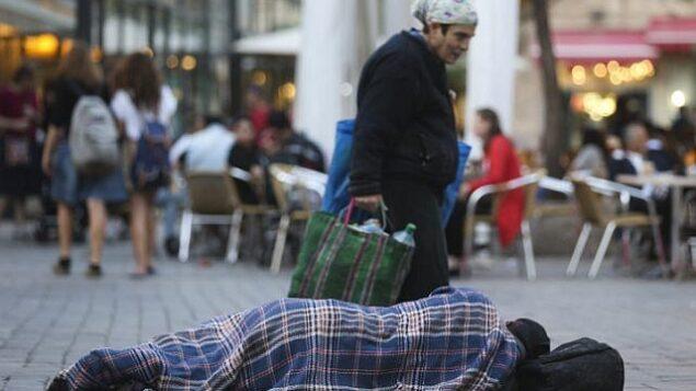 أشخاص يمرون من أمام رجل مشرد بالقرب من مقاهي في وسط مدينة القدس، 10 نوفمبر، 2013.  (Nati Shohat/FLASH90)