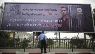 عنصر في شرطة 'حماس' ينظر إلى لوحة إعلانية في غزة للجناح العسكرية للحركة تحمل صورة الجندي الإسرائيلي أورون شاؤرول، الذي قُتل في حرب غزة 2014، 29 ديسمبر، 2017.  (Wissam Nassar/Flash90)